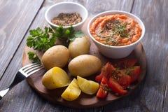 Unga potatisar kokade i en peel med zucchinikaviaren, kryddor, nya tomater och persilja Royaltyfri Bild
