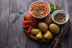 Unga potatisar kokade i en peel med zucchinikaviaren, kryddor, nya tomater och persilja Royaltyfri Fotografi