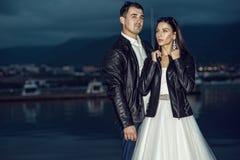 Unga precis gifta härliga stilfulla par i svarta läderomslag som står på hytten i fjärden på skymning royaltyfria foton