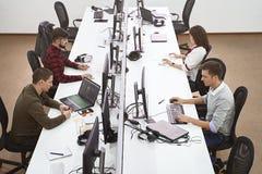 Unga professionell som arbetar i modernt kontor Grupp av b?rare eller programmerare som sitter p? fokuserade skrivbord p? datorer royaltyfria bilder