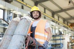 Unga rörande gascylindrar för manuell arbetare i metallbransch Arkivfoto