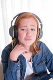 Unga redhaired flickaist som lyssnar med hörlurar Arkivbilder
