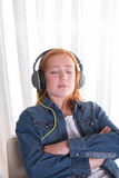 Unga redhaired flickaist som lyssnar med hörlurar Fotografering för Bildbyråer