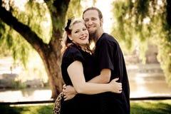 Unga retro par som kramar i park Arkivfoto