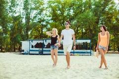 Unga roliga grabbar i solglasögon på stranden Vänner tillsammans Royaltyfri Foto