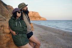 Unga romantiska handelsresande som ser till strandhimlen som tycker om solnedgången på havet - förälskelse, sommar och loppbegrep royaltyfri fotografi