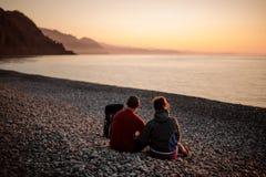 Unga romantiska lyckliga par som sitter på stranden royaltyfria foton