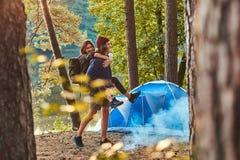 Unga romantiska par har gyckel i sommarskog n?ra deras t?lt arkivbild