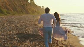 Unga romantiska par - nätt flicka i långt ljus - rosa färger klär, och den stiliga mannen kör playfully längs coastine på den san lager videofilmer