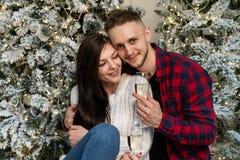 Unga romantiska par som firar nytt år nära julgranen arkivfoton