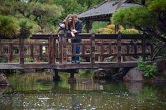 Unga romantiska par som kramar på bron som ser på vattnet Arkivbild