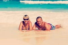Unga romantiska par som lägger på den sandiga stranden arkivbild