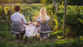 Unga romantiska par som sitter på en tabell med vin och mellanmål som beundrar vingården Romantisk matställe arkivbild