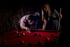 Unga romantiska par som spelar billiardleken arkivbild
