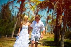 Unga romantiska par som spelar och har gyckel på stranden arkivfoto