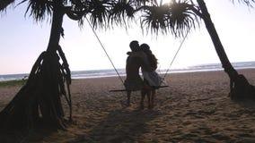 Unga romantiska par som tillsammans sitter på gunga på den tropiskt stranden och krama för hav Förälskad avslappnande för par och arkivfilmer