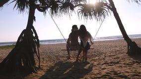 Unga romantiska par som tillsammans sitter på gunga på den tropiskt stranden och krama för hav Förälskad avslappnande för par och Arkivbilder