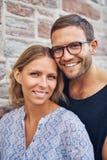 Unga söta par som ler på kameran royaltyfria bilder