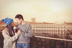 Unga söta romantiska par som dricker kaffeanseende på terrass arkivfoto