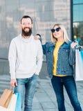 Unga shoppa påsar för stads- consumerism för par pappers- arkivfoto