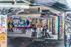 Unga skateboradåkare sitter bland grafitti av Southbank som skridskon parkerar, London Arkivbilder
