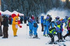 Unga skidåkare som förbereder sig att skida, och mus i dräkt Fotografering för Bildbyråer