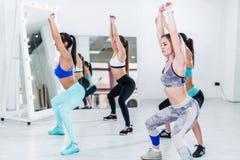 Unga spensliga kvinnor som gör över huvudet satt övning under grupputbildning i idrottshall Arkivfoto