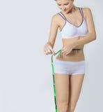 Unga sportar en härlig slank kvinna som mäter trevliga höfter för perfekt form, begreppet av en sund livsstil på en vit bakgrund royaltyfria foton