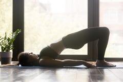 Unga sportiga görande pilates eller den yogaGlute bron poserar royaltyfri fotografi