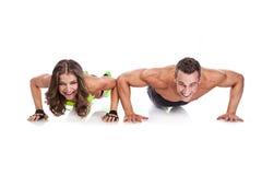 Unga sportiga par för härlig kondition som gör liggande armhävningar Royaltyfri Fotografi