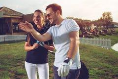 Unga sportive par som spelar golf p? en golfbana arkivfoto