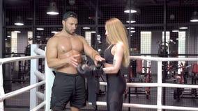 Unga sportpar avslutade utbildning i boxning och att ta boxas av handskar i cirkeln arkivfilmer