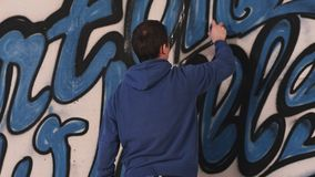 Unga stads- målareteckningsgrafitti på väggen Arkivbild