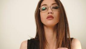 Unga stilfulla brunettaffärskvinnor som bär exponeringsglas på den vita bakgrunden lager videofilmer