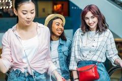 Unga stilfulla kvinnor som tillsammans går i shoppinggallerian, unga flickor som shoppar begrepp Royaltyfri Foto