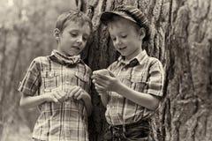 Unga stilfulla pojkar bläddrar internet på mobil p Royaltyfri Foto