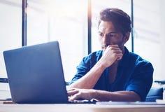 Unga stiliga bankrörelsen finansierar analytikeren som arbetar på det soliga kontoret på bärbara datorn, medan sitta på trätabell royaltyfri fotografi