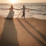 Unga stiliga brud- par som promenerar stranden på soluppgång Arkivbilder