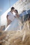 Unga stiliga brud- par som utomhus delar ett ögonblick Arkivfoton