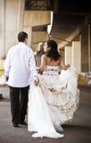 Unga stiliga brud- par som utomhus går i stadsområde Royaltyfria Bilder