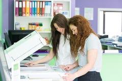 Unga studenter på en kopieringsmitt arkivbild