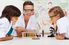 Unga studenter som håller ögonen på ett experiment i elementära vetenskapsclas Arkivfoto