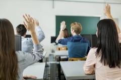 Unga studenter som lyfter händer i ett klassrum Royaltyfri Fotografi