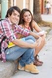 Unga studenter som sitter i gatainnehavet, bokar. Arkivbilder