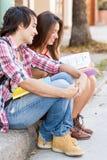 Unga studenter som sitter i gatainnehavet, bokar. Arkivfoto