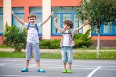 Unga studenter, två siblingbröder som går till skolan Royaltyfria Bilder