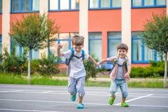 Unga studenter, två siblingbröder som går till skolan Arkivbild