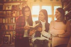 Unga studentflickor i arkivläsebok tillsammans och royaltyfri bild