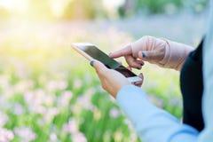Unga studentkvinnor som direktanslutet shoppar på smartphonen, medan handledhanden smärtar affär och modernt livsstilbegrepp arkivfoton