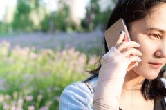 Unga studentkvinnor som kallar på smartphonen, medan handledhanden smärtar begreppssoffa som tycker om den moderna nätt vita kvin Arkivfoto